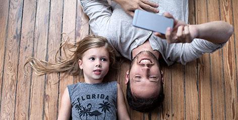 Vater schaut mit Tochter auf ein Smartphone