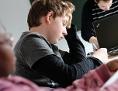 Ein Schüler lernt mit angestrengtem Gesichtsausdruck in einem Lerninstitut