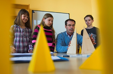 Ein Lehrer und drei Volksschulkinder üben Mathematik