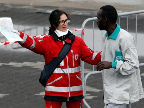 Eine Mitarbeiterin des Roten Kreuzes zeigt einem Flüchtling den Weg