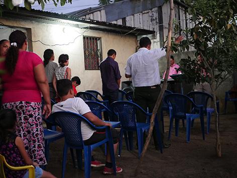 """Etwa 15 Gläubige bei einem Gottesdienst in einer """"Gartenkirche"""" in Lateinamerika"""