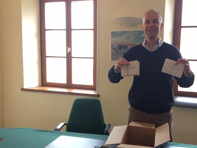Der Bürgermeister hält Wahlzettel hoch