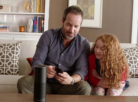 Ein Mann und ein Kind blicken auf Amazons Echo Lautsprecher