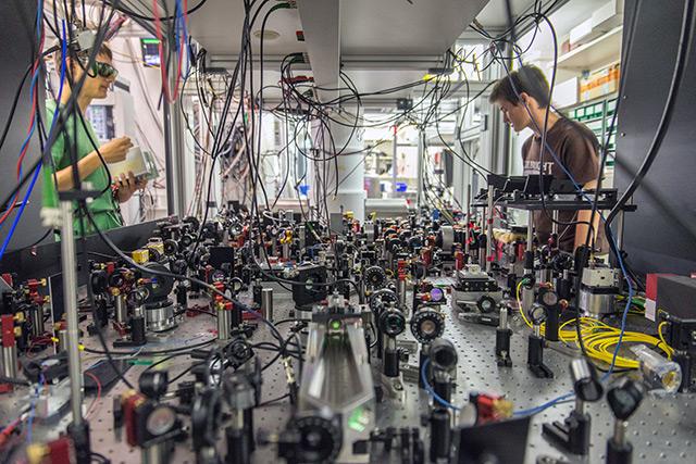 Labor: Forscher neben Versuchsaufbau mit optischen Geräten und einem wohlgeordenetem Kabelsalat