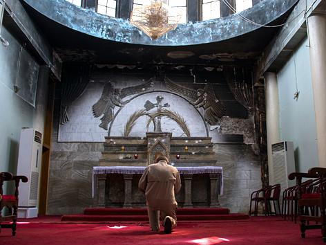 Ein Gläubiger kniet vor dem Altar einer Kirche in Karakosch, Irak