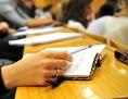 Eine Studentin schreibt während einer Vorlesung in einem vollen Hörsaal mit.