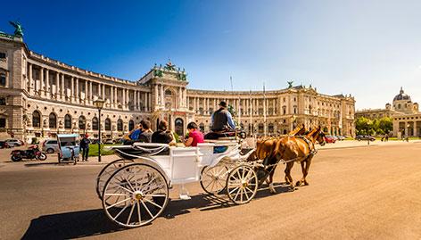 Touristen fahren in einem Fiaker durch Wien