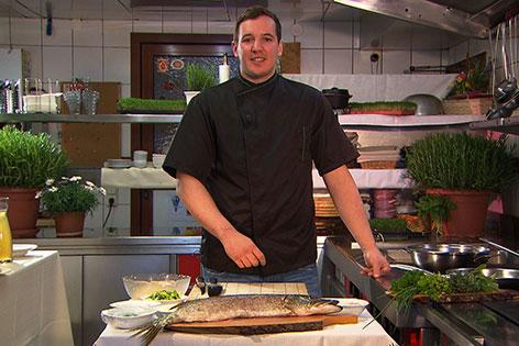 Johann Weindl mit Seehecht in der Küche