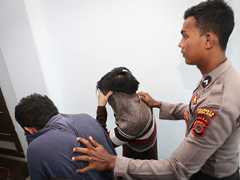 Zwei junge Männer werden von einem indonesischen Polizisten abgeführt werden
