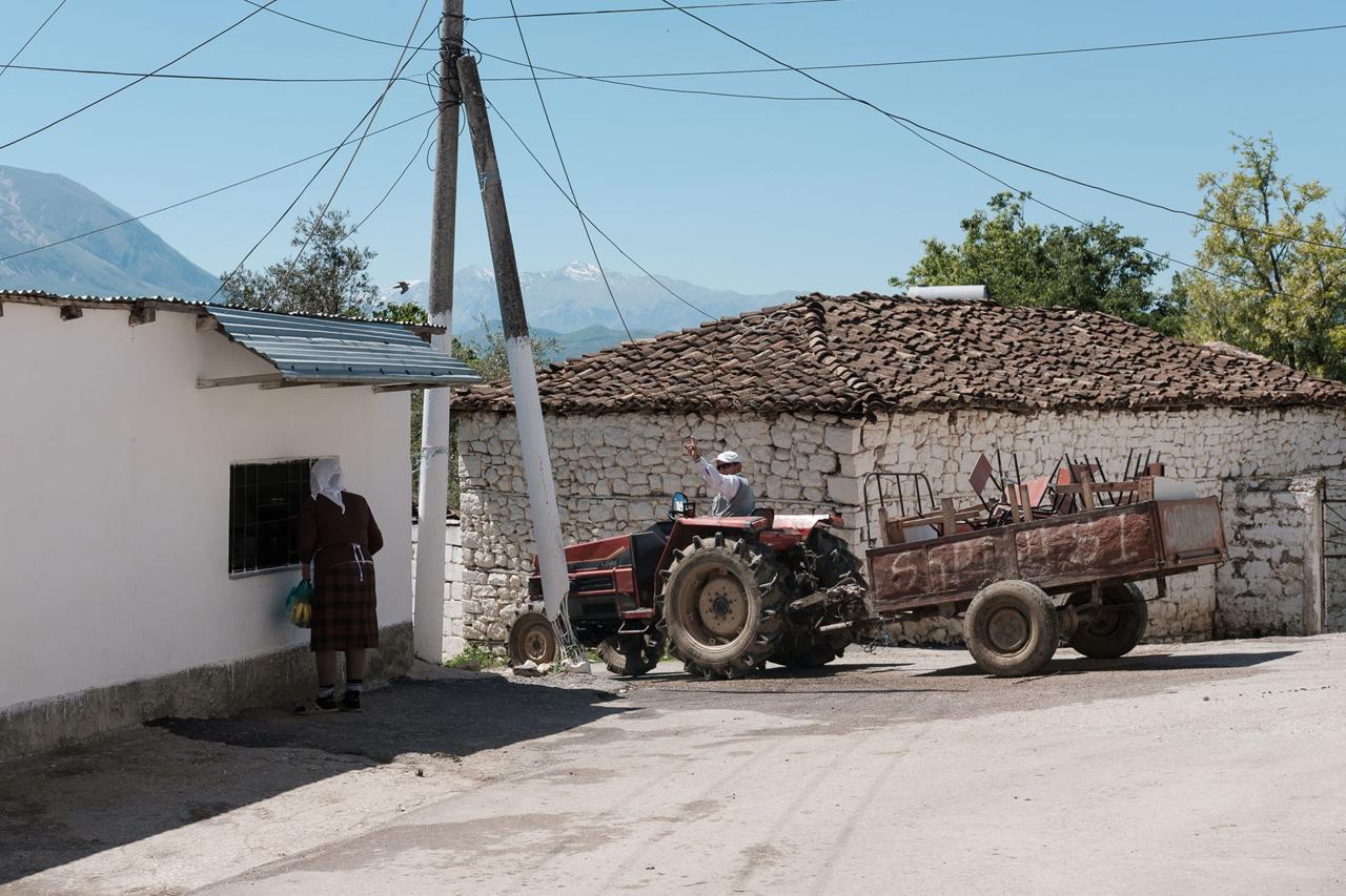 Dorf: Traktorfahrer grüßt Frau