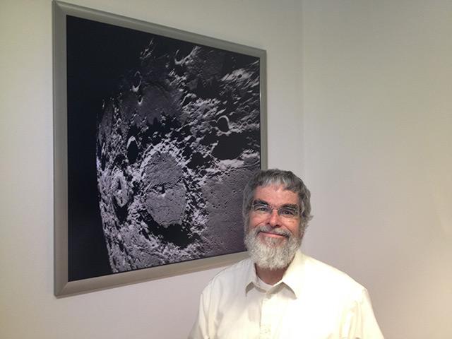 Guy Consolmagno vor einem Bild des Mondes