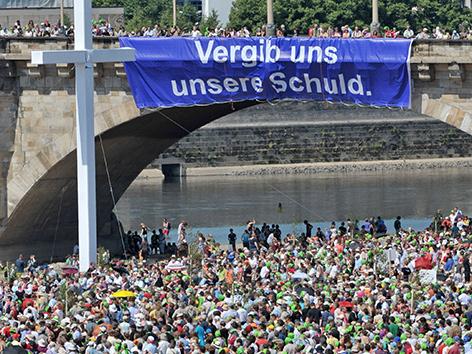 """Menschenmassen am evangelischen Kirchentag in Dresden 2011. Auf einer Brücke hängt ein großes Transparent mit der Aufschrift: """"Vergib uns unsere Schuld""""."""
