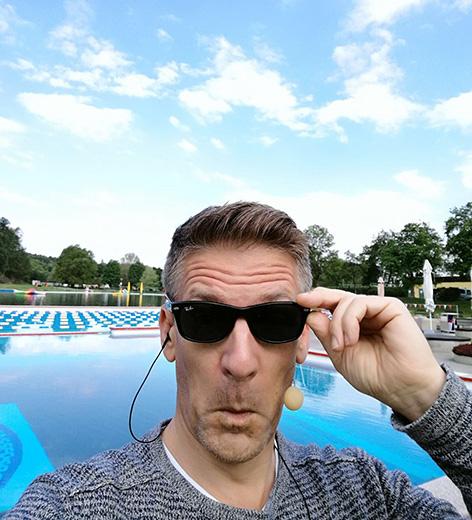 Andi Knoll mit Sonnebrille vor Schwimmbecken