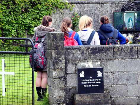 Mädchen am Gedenkschrein vor dem ehemaligen Mutter-Kind-Heim in Tuam, Galway County in Irland