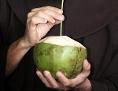 Ein Mann trinkt aus einer Kokosnuss