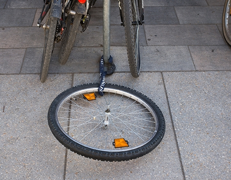 ein angekettes Vorderrad ist von einem gestohlenen Fahrrad übriggeblieben