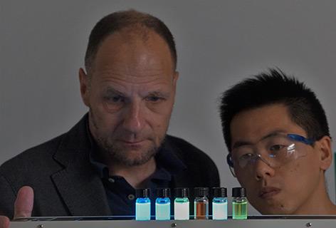 Labor: Forscher stehen vor leuchtenden Fläschchen