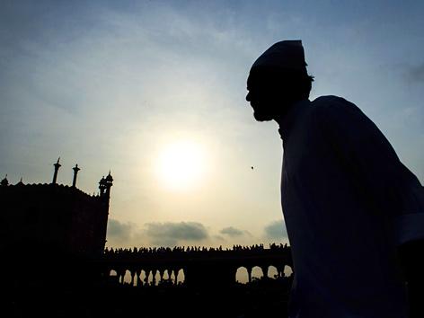 Ein Muslim im Dämmerlicht vor der Jama-Moschee in New Delhi, Indien