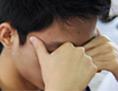 Ein Jugendlicher hält sich die Hände vors Gesicht, er hat Kopfweh