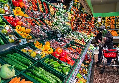 Eine Supermarkt-Kundin steht vor dem Obst- und Gemüseregal und packt frisches Gemüse in einen Einkaufskorb