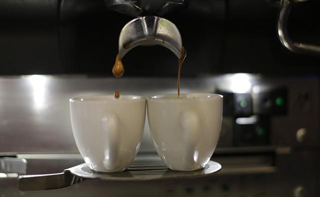Kaffee tropft in zwei Espressotassen