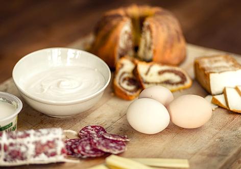 Joghurt, Eier, Wurst, Käse, Kuchen auf einem Brett