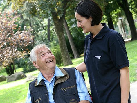 Ein älterer Herr im Rollstuhl mit einer Betreuerin im Park