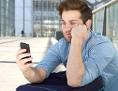 Junger Mann blickt genervt auf sein Smartphone