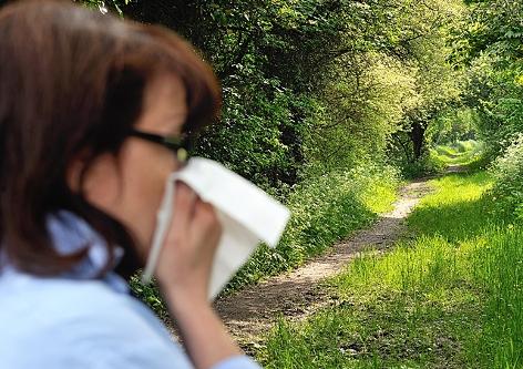 Eine Frau steht im Wald und niest