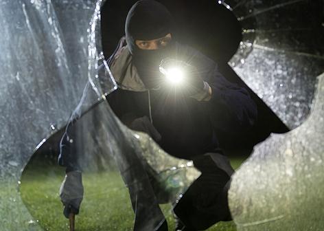 Ein Einbrecher blickt durch eine eingeschlagene Fensterscheibe