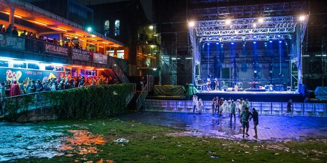 Menschen im Regen vor einer leeren Bühne