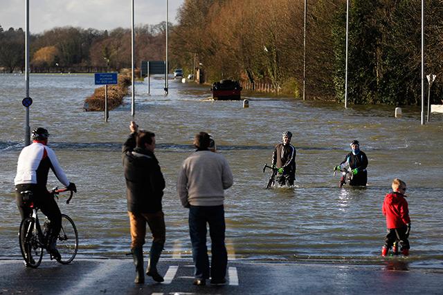 Radfahrer waten durch Hochwasser