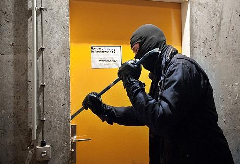 Ein Mann hebelt mit einem Brecheisen eine Tür auf