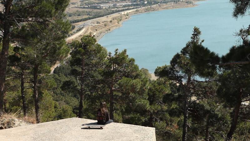 Skateboarderin sitzt auf Felsen