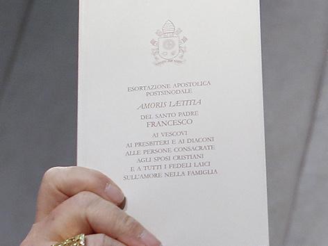 Ein Kardinal hält das Dokument Amoris Laetitia zu Ehe und Familie