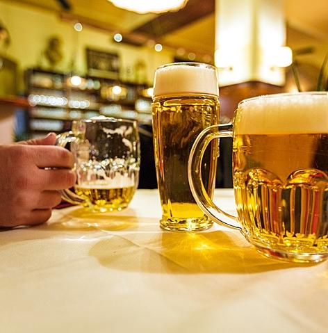 Gefüllte Biergläser und Krüge auf einem Tisch