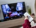 Eine Frau sitzt mit der Fernbedienung in der Hand auf der Couch und schaut fern