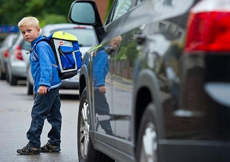 Ein Bub übt das sichere Queren einer Straße