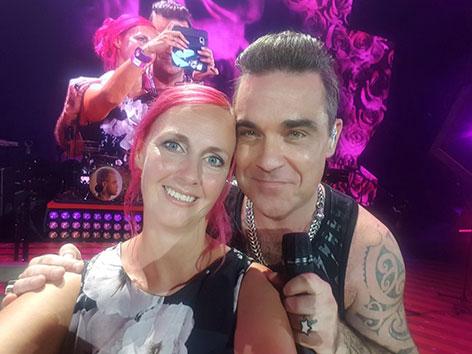 Robbie Williams und Fan Michaela auf der Bühne in Klagenfurt
