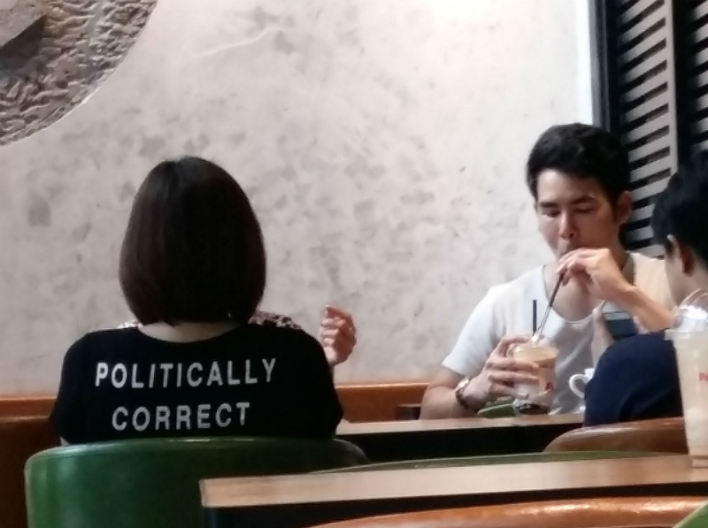 "Frau in Café mit T-Shirt-Aufdruck ""Politically correct"""