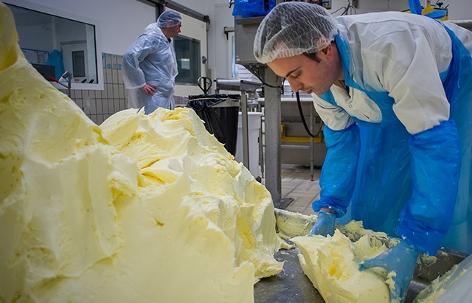 Ein Arbeiter teilt einen großen Block Butter in kleinere Teile
