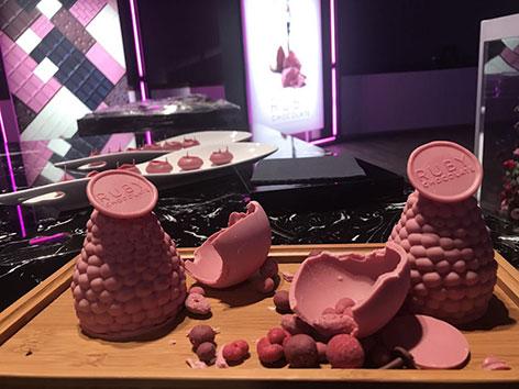 rosa-rote Schoko-Kreationen auf einem Holztisch