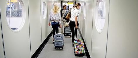 Flugpassagiere mit Trolleys am Gate