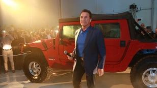 Arnold Schwarzenegger vor einem roten Elektro-Hummer