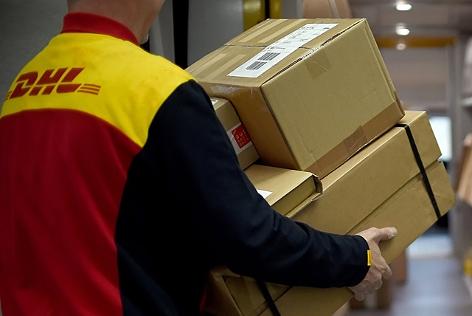 ein DHL-Mitarbeiter trägt Pakete