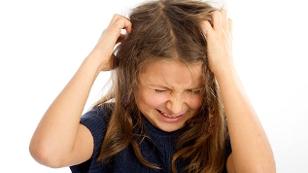 Mädchen mit Kopfläusen rauft sich die Haare