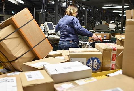 eine Mitarbeiterin sortiert im Paketzentrum des Logistikkonzerns DHL Pakete