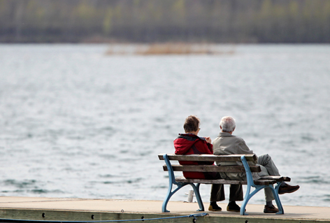 Senioren-Paar auf Bank am See