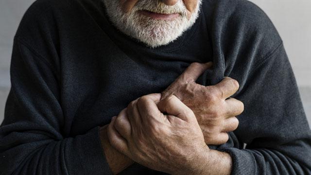 Mann hält sich den Brustkorb