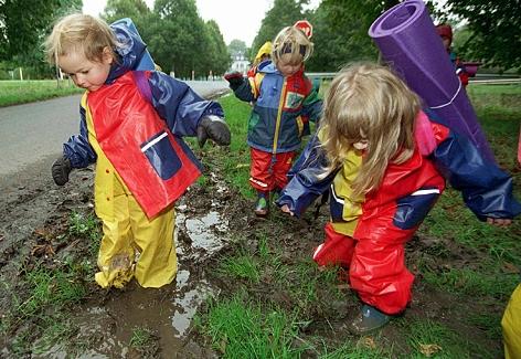 Kindergartenkinder spielen in einer schlammigen Pfütze